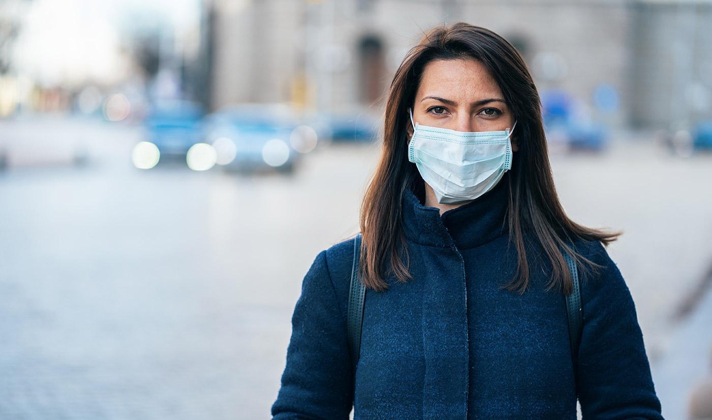 A woman wearing a face mask walking outside