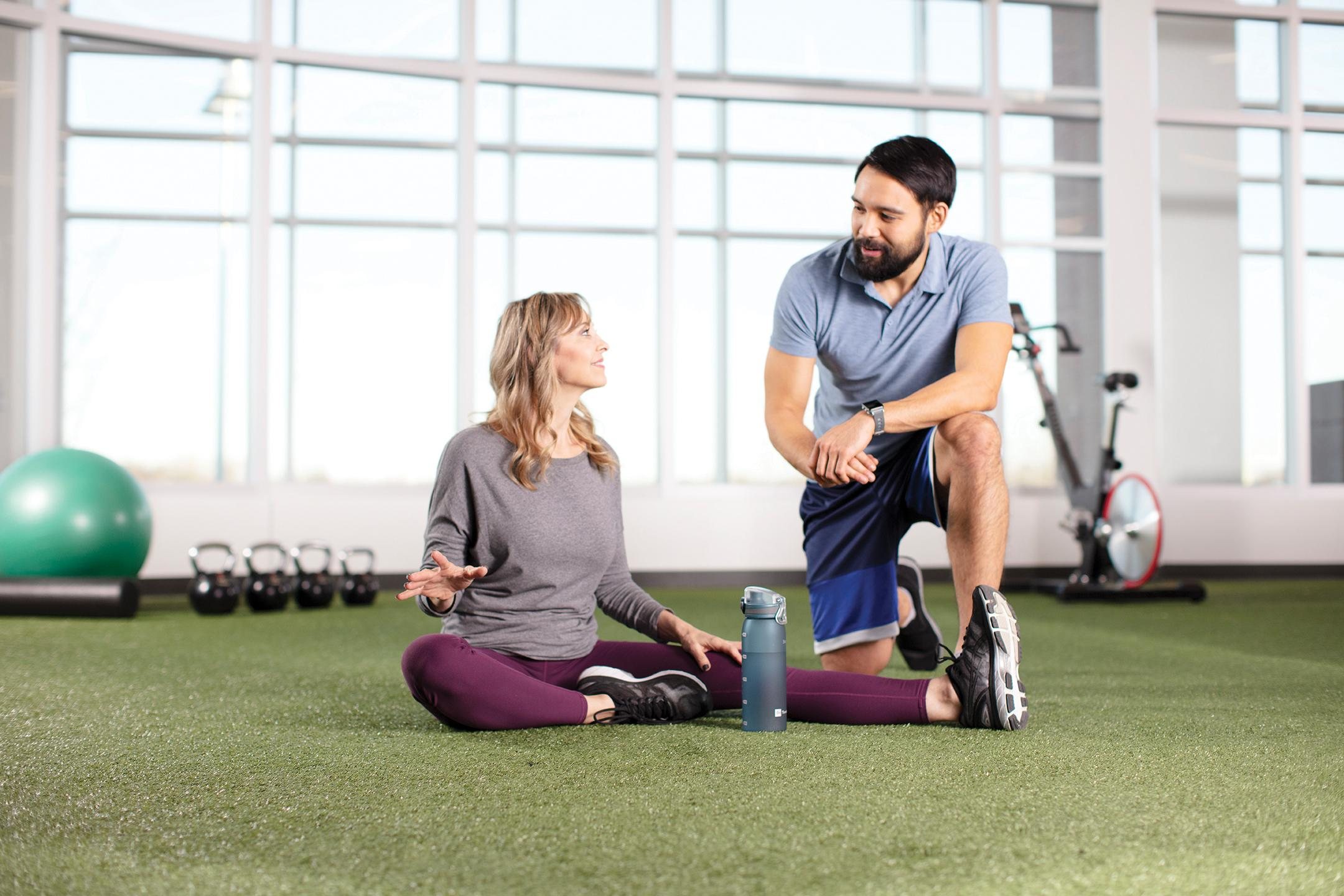 People smiling in workout clothes on some sort of astroturf?